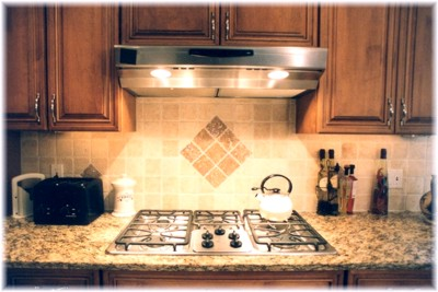 Detail of the cooktop, hood and custom, tiles backsplash...